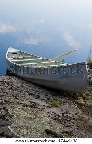 A lone canoe sitting on a rocky shore in Northern Ontario.