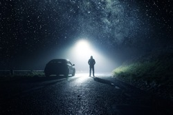 A lone car, parked on the side of the road with a hooded figure, on a spooky country road. With a bright light and stars at night.