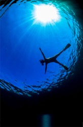 A lone diver in the abyss of the ocean. Deep sea diver. Diver in the water under the sun. Diver underwater