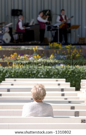 A lone elderly woman watching a jazz band in the Kurpark, Bad Homburg - Germany. Selective focus on lady.