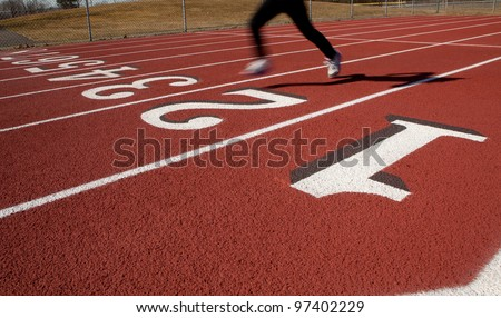 A lone female runner on a ruberized track at the start/finish line