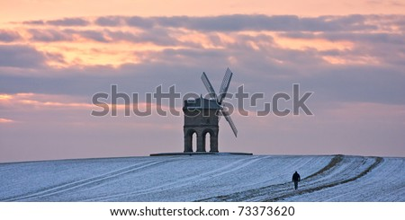 A lone figure walking in a snowy winter landscape at sunset at Chesterton windmill in Warwickshire, England.