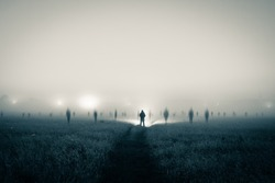 A lone figure with a torch standing in a field as ghostly blurred figures appear on a spooky, misty night. With a duo tone high contrast edit.