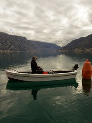 A lone fisherman in the middle of the Bay of Kotor in a white traditional barge points to Kotor with his other hand holding a fishing rod. Against the backdrop of mountains and clouds. Peace and quiet
