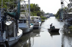 A lone fisherman poles a flatboat along a canal in Lafitte, Louisiana, lined with shrimp boats.