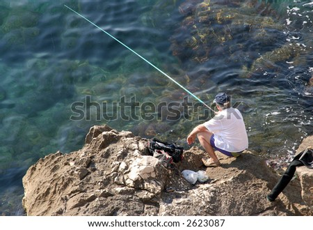 a lone fisherman sitting on the rocks in marseille bouches du rhone france europe