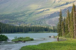 A lone fly fisherman gets ready to cast in the valley with trees and mountains surrounding him