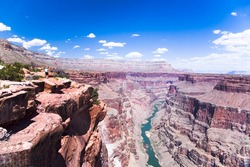 A LONE HIKER VIEWS The COLORADO RIVER FROM THE NORTH RIM OF THE GRAND CANYON AT THE TOROWEAP OVERLOOK