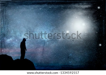 A lone hooded figure silhouetted, standing on a hill looking at a galaxy at night with UFOs floating in the sky. With a grunge, vintage edit.
