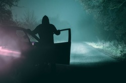 A lone, hooded figure standing next to a car looking at an empty misty winter country road silhouetted at night by car headlights. With a cold, grainy, muted edit.