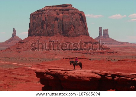 A lone indian rider sits on his horse in front of the famous rock formations of Monument Valley in Arizona,
