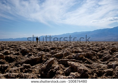 A lone man stands in the distance of the Devil's Golf Course in Death Valley National Park.