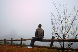 A lone men sitting in the fog on the mountain
