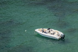 A lone motor boat with a man sitting in it in the middle of the sea. Copy space.
