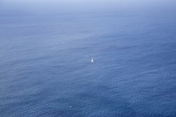 A lone sail boat sailing in the oceans near Cape Point, South Africa
