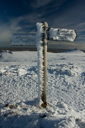 A lone sign post stands among winter snow on top of Bennachie.  Prevailing winds have iced its left side, while its right is clear.  Ice also cakes the finger pointers against a wispy clouded blue sky