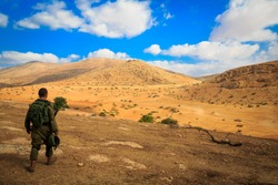 A lone soldier walks through the desert after a long training session