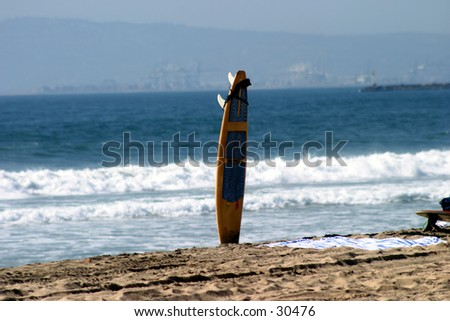a lone surf board sits in the sand with the blue ocean and white waves in the background waiting for its owner to come back to go surfing