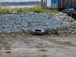 A lone tire sitting by a rock wall. The garbage sitting on top of the gravel also includes lobster cages and random sheets of rubber.