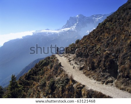 A lone trekker walks along a perfect mountain trail in the Himalaya, Nepal