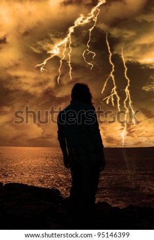 a lone woman looking sadly over the cliffs edge in county clare ireland during a thunder storm