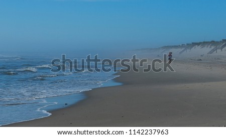 A lone woman runner, ponytail flying, runs down an early morning beach, away from the camera into the horizon's haze, flanked by a gentle surf, and distant dunes and sea grass, Outer Banks, NC 2018