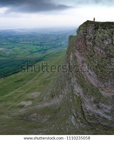 A lone woman stands overlooking the valley on a mountain top cliff stock photo