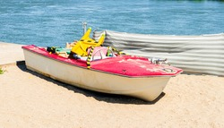 A lonely, abandoned boat on the sandy beach.