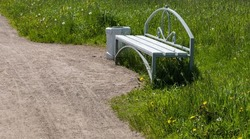 a lonely bench in the park for recreation. trash can next to the bench
