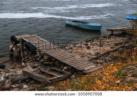 a lonely blue boat is tied with a chain. wooden pier for boats #1058907008