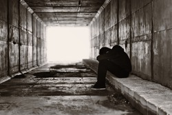 A lonely boy sits on a curb on the right side of a tunnel