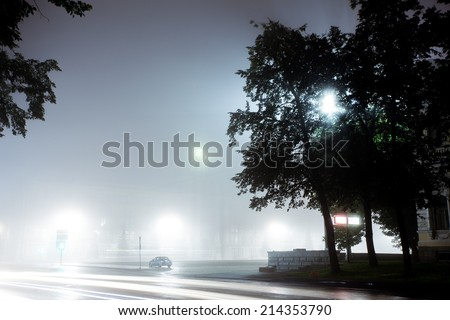 A lonely car drives along empty city street at night after rain. Street is filled with neon light blurred with fog