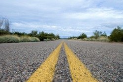 A lonely deserted road in the middle of the desert.  The image uses a radial blur to provide the effect of motion.