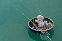A lonely fisherman used only crude fishing gear was waiting patiently inside his round bamboo boat along the calm estuary at Danang, Vietnam.