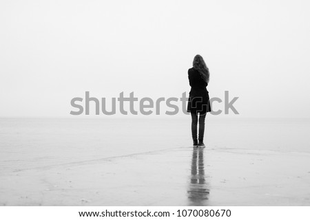 A lonely girl looks out into the distance in the rain. Black and white. Loneliness #1070080670