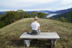 A lonely girl sits on a wooden bench at the top of a mountain. There is a lake view but she stares at the ground.