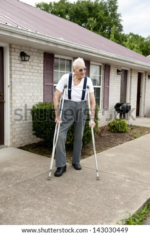 A lonely handicapped elderly man with crutches standing outside his apartment