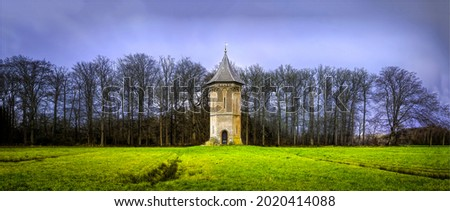 A lonely high tower in a field. High tower in field. Panorama of tower in field