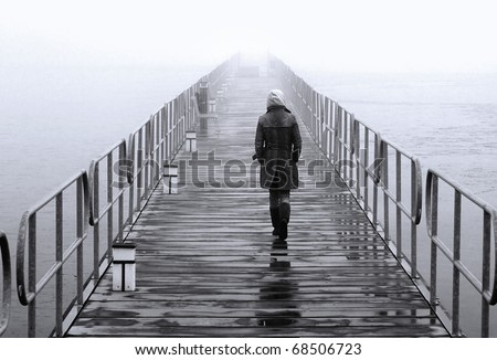 A lonely lady crossing the floating pedestrians' bridge that leads to the islet of Aghios Achilleios in Mikri Prespa lake