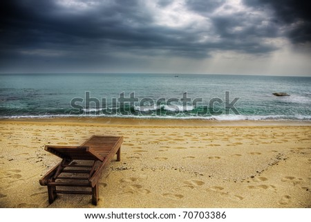 a lonely lounger on the stormy beach