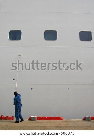 A lonely man painting a large ship