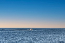 A lonely motor boat sails in the sea. Lonely boat, movement on the water. Calm water surface with horizon line background