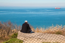 A lonely old man looking the sea from the back. Rear view of senior man sitting and looking the horizon.
