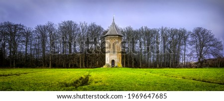 A lonely old tower in a field. Old secluded tower. Panorama of old tower. Tower