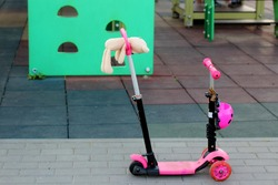 a lonely pink scooter with a forgotten toy on the handle near the playground in summer