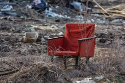 A lonely red chair stands in the background of the trash.  Somewhere in the forest.  Garbage. garbage from the village.