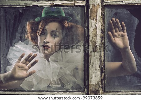 A lonely sad pierrot woman behind the glass
