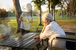 A lonely senior woman is waiting and thinking old memories of her family that will visit her again,depressed elderly people with loneliness and depression sitting alone,missing,nostalgia,remembrance