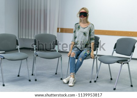 a lonely sitting woman with blindfold sits on one of the chairs #1139953817