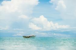A lonely small boat floating in beautiful tropical ocean, Thailand.